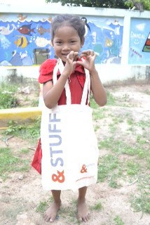 Cambodian girl with an &Meetings bag Round her Neck