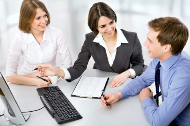 Two Business Women Showing Businessman Something on a Computer
