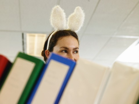 Woman Wearing Bunny Ears with half her Face Covered by Books