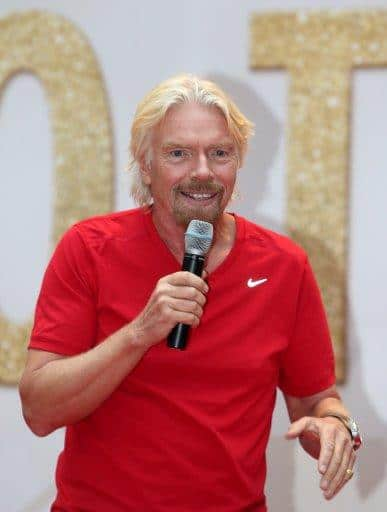 Richard Branson Wearing a red top Speaking into a Microphone