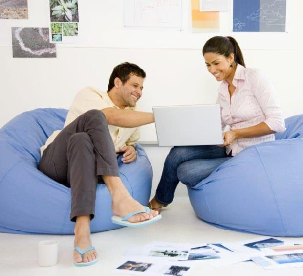 Man and Woman Laughing, Looking at a Laptop Whilst sat in Beanbags
