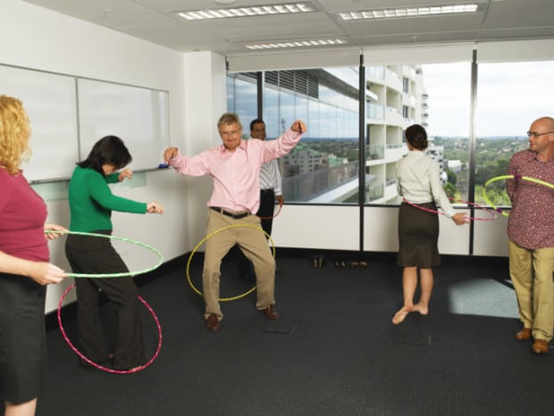 People Doing Hula Hooping in an Empty Office Room