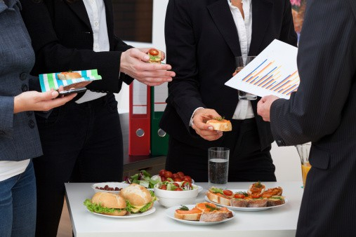 Business People Taking Food off a Small Table