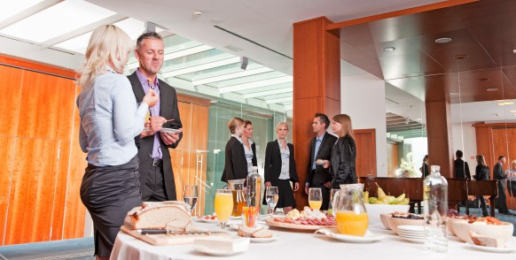 Business People Stood Near a Table Full of Food and Drinks