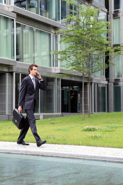 Businessman on the Phone Walking Past a Modern Building and Tree