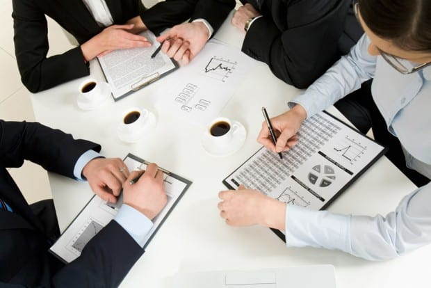 Business People Writing on Paper with Graphs in a Meeting