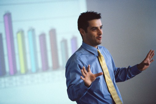 Man Giving Presentation with Projected Graph Behind him