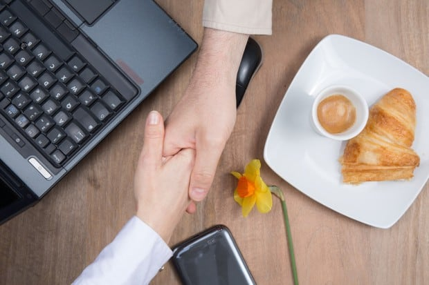 Two People Shaking Hands Over a Desk with a Croissant on it