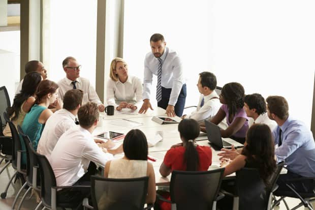 Large Business Meeting Being led by man Leaning on Table