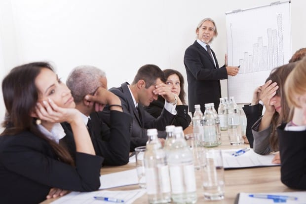 Business People Uninterested whilst sat in a Meeting