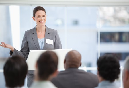 Business Woman Giving Presentation Smiling with one Raised Hand