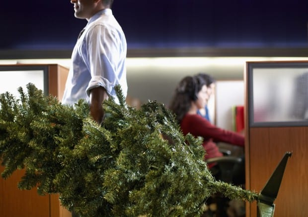 Businessman Carrying a Small Christmas Tree Through an Office