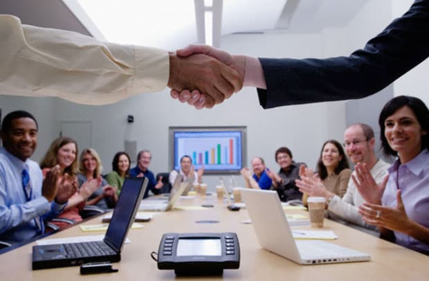 People Shaking Hands in a Meeting While Everyone Else Claps