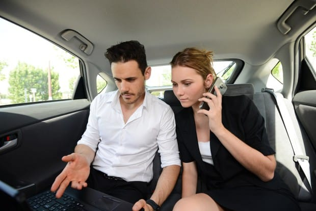 Man and Woman Looking at a Laptop in a car