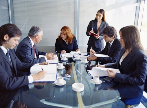 Business People Meeting in Conference Room with a Woman Standing Behind Them Making Notes