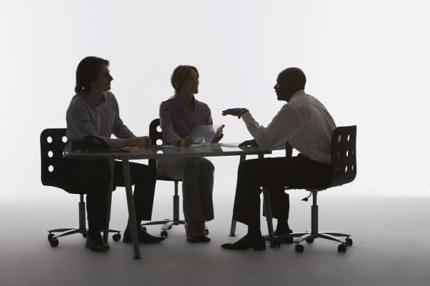 Dark Image of a man Interviewing a man and a Woman