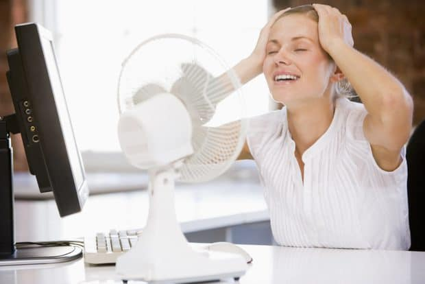 Businesswoman in Office With Computer Cooling off With a Fan