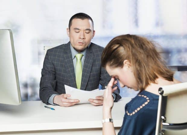 A Business man Looking at a CV Questioningly and a Woman With her Head Down