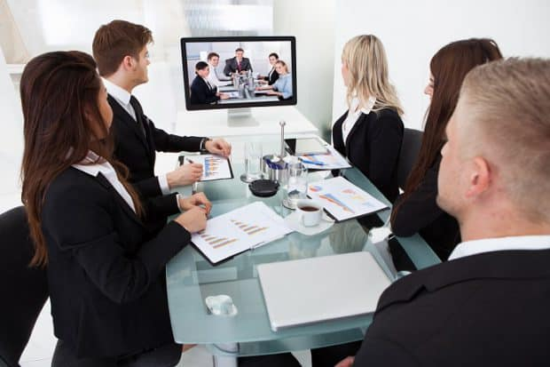 Business People Attending Video Conference at a Desk