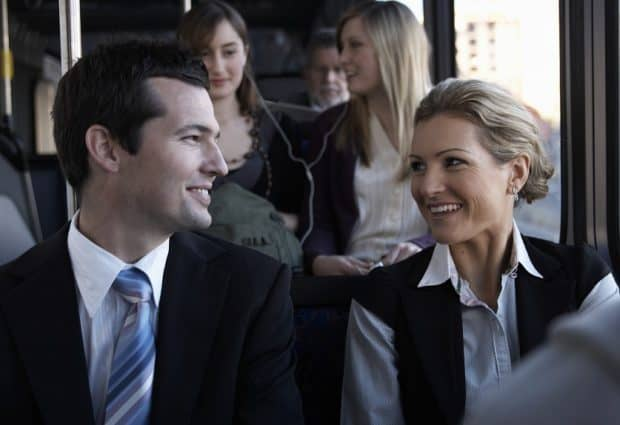 Businessman Smiling at a Woman on a bus