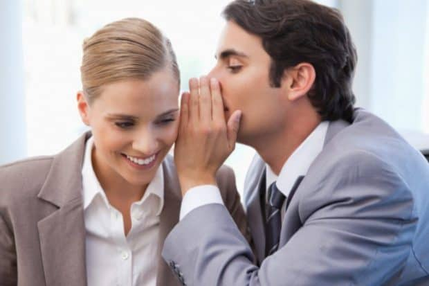A Business man Whispering Something Into a Woman's ear