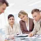 Team members sitting around meeting room table