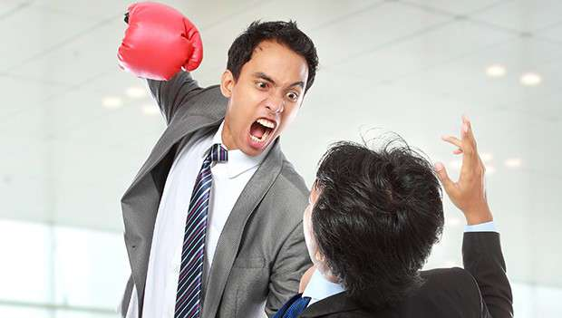 Meeting attendee with a boxing glove about to punch a fellow businessman