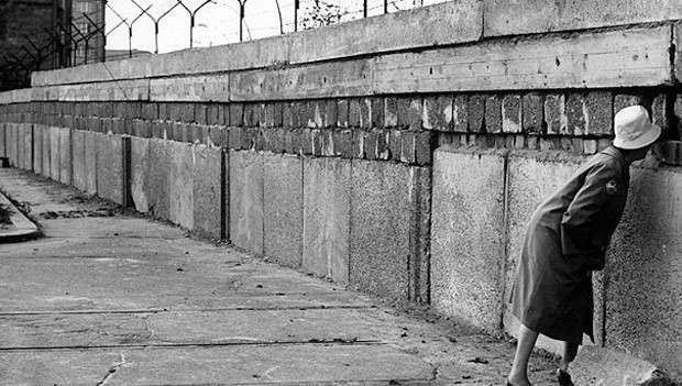 Old image of lady peering through the Berlin Wall