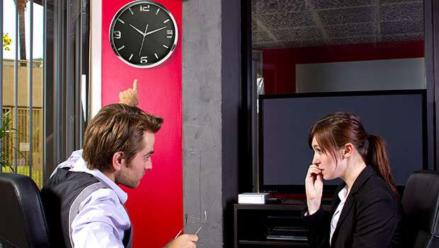 Female office worker being taken to task over bad time keeping